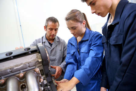 service engineer: Students with instructor working on auto engine