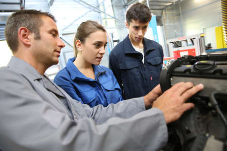 repair garage: Students with instructor working on auto engine