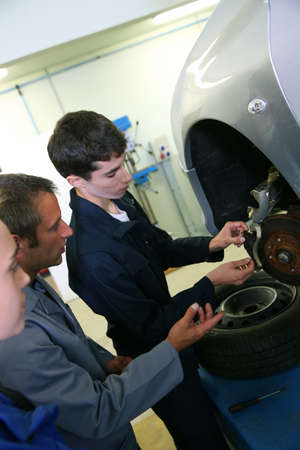 Instructor showing students how to repair car wheel photo