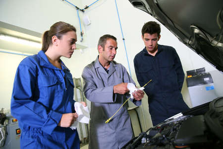 service engineer: Instructor with students in repairshop changing motor oil