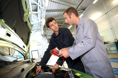 diagnostic tool: Trainer with student in repairshop checking on battery