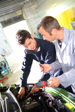 Trainer with student in repairshop checking on battery Stock Photo - 20690890