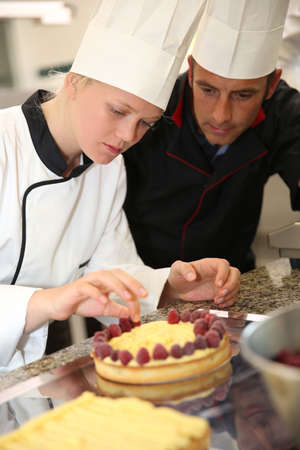 Pastry cook teaching student to make a cake Stock Photo