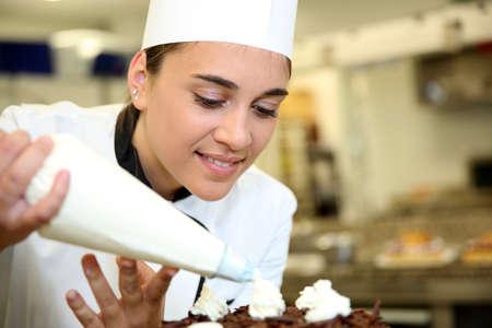 slagroom: Banketbakker zetten slagroom op de taart