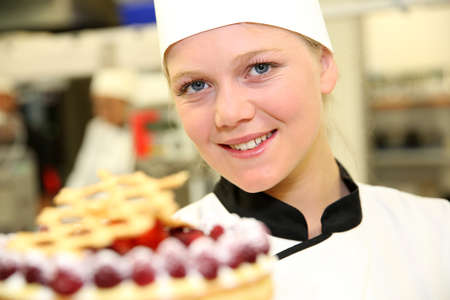 Portrait of young confectioner holding cake photo