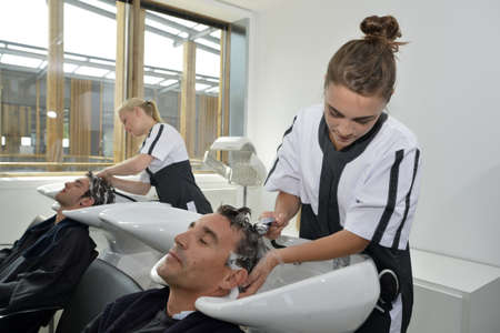 Young women in hair salon washing customers hair photo