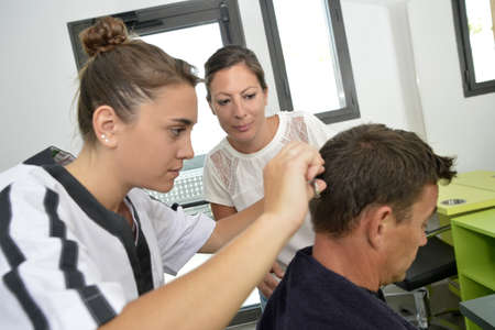 hairdressing: Hairdressing student girl learning how to cut hair