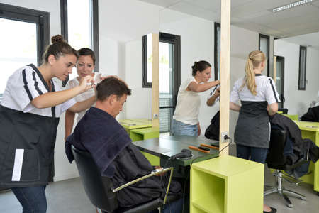 Hairdressing student girl learning how to cut hair photo