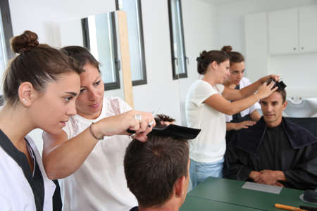 Student girl in hairdressing learning how to cut hair photo