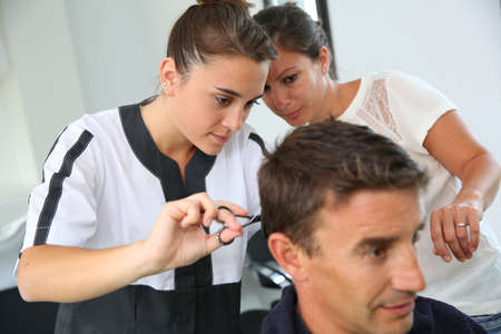 Student girl in hairdressing learning how to cut hair