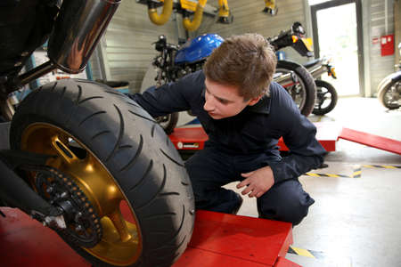 Teenager in professional training, repairing motorbike photo