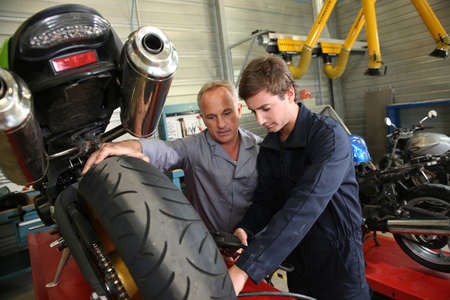 vocational: Teacher with students in mechanics working on bike