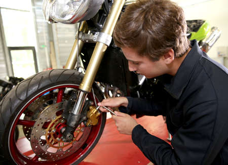 Teenager in professional training, repairing motorbike Stock Photo