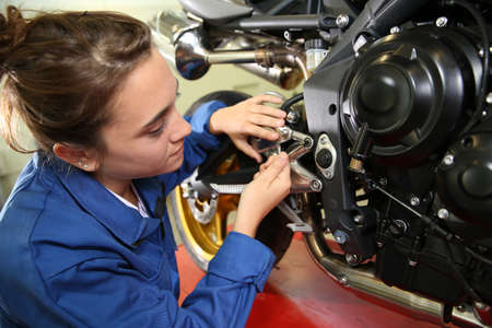 service engineer: Student girl in motorbike mechanics