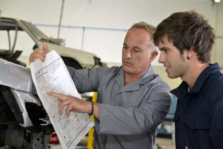 job engine: Teacher with coachbuidling student in repairshop Stock Photo