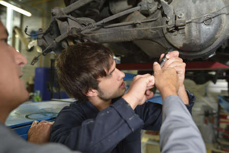 Mechanics teacher with student in car repairshop photo