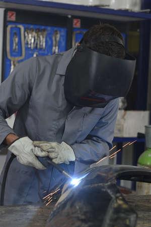 maching: Closeup of solderer fixing bodywork