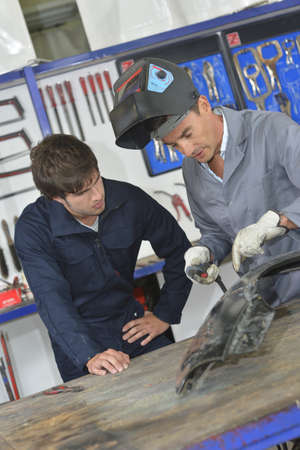 Trainee with instructor using welding machine photo