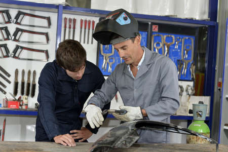 vocational: Trainee with instructor using welding machine
