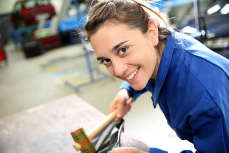 coachwork: Coachbuilding sudent working on car in repairshop Stock Photo