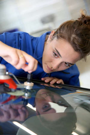 windscreen: Young student in bodywork changing car windshield Stock Photo