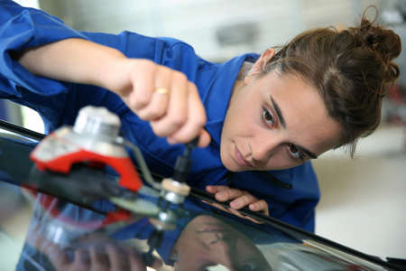 vocational: Young student in bodywork changing car windshield Stock Photo