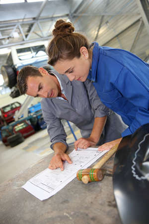 coachwork: Instructor with student girl looking at bodywork instructions