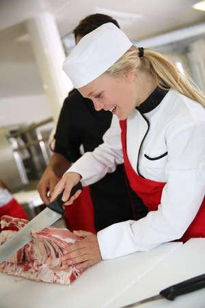 jasschort: Meisje snijden vlees tijdens slager opleiding