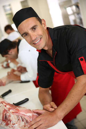 Portrait of smiling butcher standing in kitchen photo