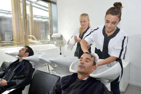 hairdress: Young women in hairdress training washing customers hair Stock Photo