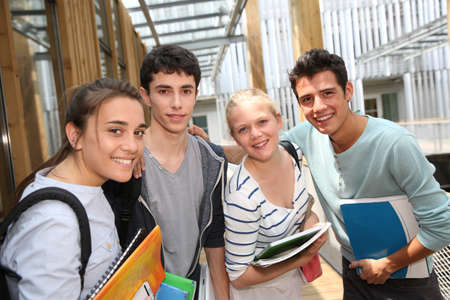 school campus: Cheerful students standing outside school building Stock Photo