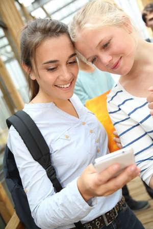 websurfing: Girlfriends websurfing on smartphone at school