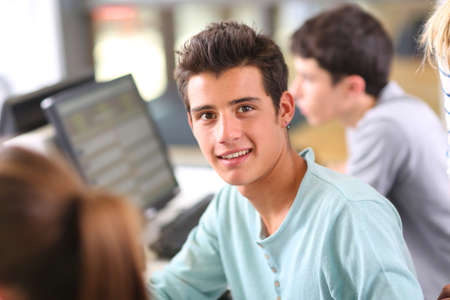 teenaged boy: Smiling teenaged boy in computing class Stock Photo