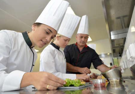 Squadra di giovani cuochi preparano piatti di specialità gastronomiche Archivio Fotografico - 20756332