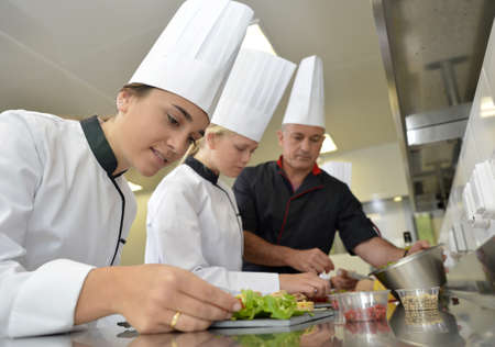 cooker: Team of young chefs preparing delicatessen dishes
