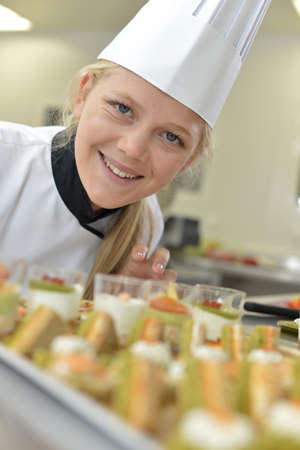 person appetizer: Young caterer preparing tray of appetizers Stock Photo