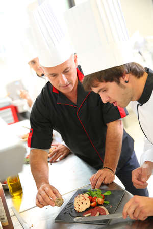gastronomy: Chef helping student in catering to prepare foie gras dish Stock Photo