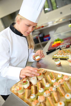 caterer: Young caterer preparing tray of appetizer