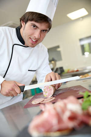 Young pork butcher cutting slice of sausage Фото со стока