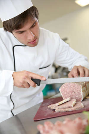 meat loaf: Young pork butcher cutting slice of meat loaf Stock Photo