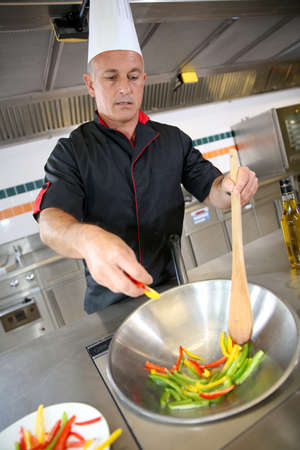 Chef in restaurant kitchen preparing wok of vegetables photo