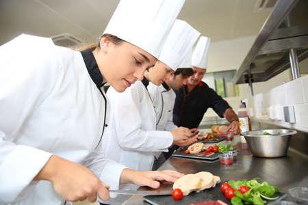 stravování: Tým mladých kuchařů připravujících lahůdky nádobí