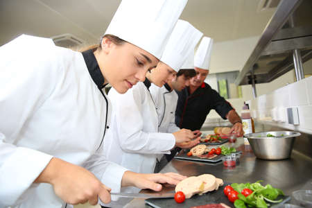 chef cooking: Team of young chefs preparing delicatessen dishes