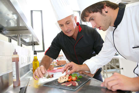 chefs: Chef helping student in catering to prepare foie gras dish Stock Photo