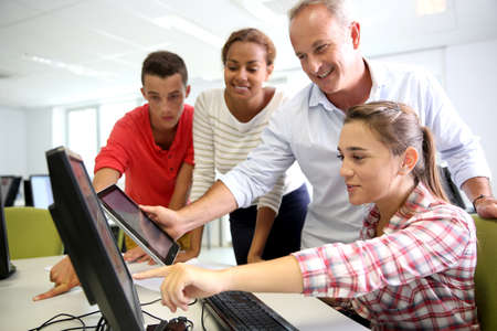 student girl: Teacher with students in computing class Stock Photo