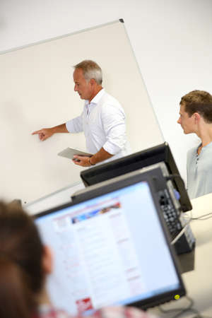 classroom training: Business school teacher doing lecture on whiteboard Stock Photo