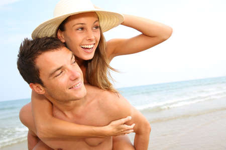 Man giving piggyback ride to girlfriend by the ocean photo