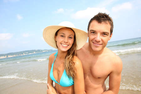 Cheerful young couple standing on the beach photo