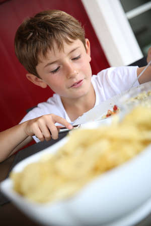 6 years: Portrait of young kid eating grilled food in summer Stock Photo