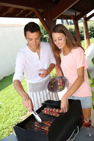 Couple cooking meat on grill at home Stock Photo